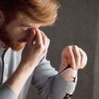 man rubbing bridge of nose